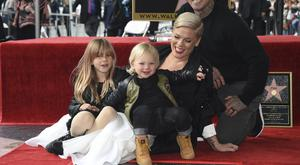 Pink poses with her husband Carey Hart, and children Willow Sage, left, and Jameson, as she is honoured with a star on the Walk Of Fame (Phil McCarten/Invision/AP)