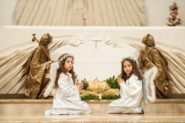 Keep the faith: Kosovar children dressed as angels at the Mother Teresa cathedral in Pristina on Christmas Eve. Photo: Getty Images