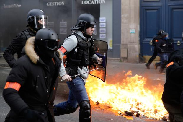 Riot police run past burning dustbins set on fire by yellow vest protesters as they keep pressure on French President Emmanuel Macron's government (AP Photo/Kamil Zihnioglu)