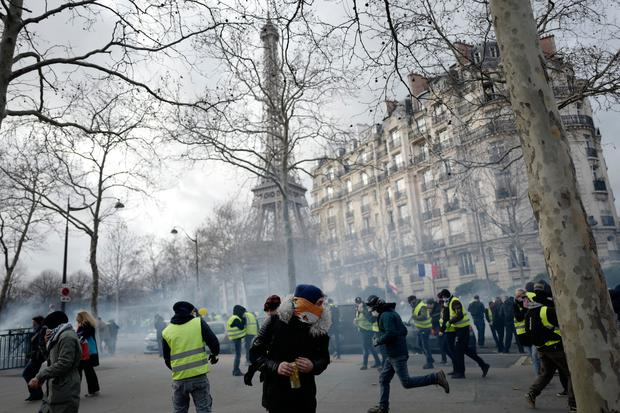 Yellow vest protesters run away from tear gas fired by riot police as they keep pressure on French President Emmanuel Macron's government (AP Photo/Kamil Zihnioglu)