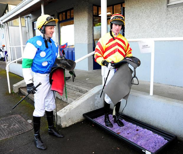 Jockeys Johnny Barry and Mark O'Hare disinfect their boots after riding at Naas yesterday. Photo: Healy Racing