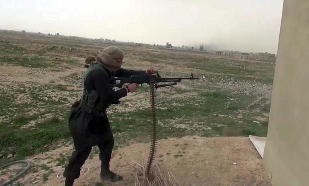 This frame grab from video posted online Friday, Jan. 18, 2019, by supporters of the Islamic State group, purports to show an IS fighter firing a weapon during clashes with members of the U.S.-backed Syrian Democratic Forces, in the eastern Syrian province of Deir el-Zour, Syria. (Militant Photo via AP)