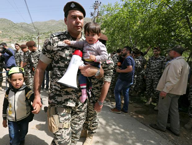 Lebanese general security member holds Syrian refugee children, who fled to Lebanon, as they wait for buses to go back to Syria from the southern village of Shebaa, Lebanon April 18, 2018. REUTERS/Aziz Taher/File Photo