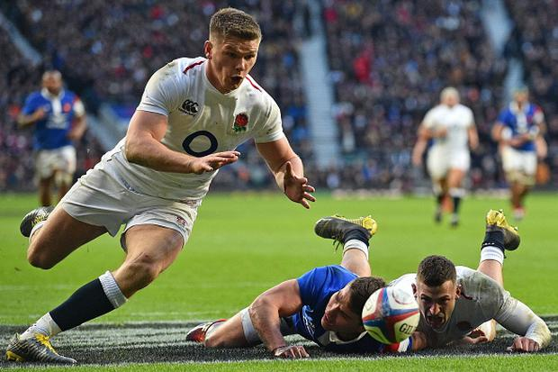 France's Antoine Dupont (C) and England's wing Jonny May (R) look on as England's fly-half Owen Farrell (L) runs in to score a try during the Six Nations international rugby union match between England and France at Twickenham. (Photo credit: GLYN KIRK/AFP/Getty Images)