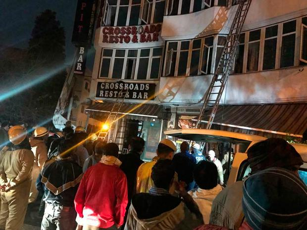 In this photo provided by Sivanand Chand, a hotel guest who was rescued, firefighters rescue people during an early morning fire at the Arpit Palace Hotel in the Karol Bagh neighborhood of New Delhi, India, Tuesday, Feb.12, 2019. More than a dozen people were killed. (Sivanand Chand via AP)