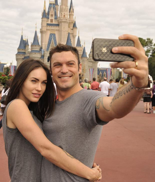 Brian Austin Green (right) and his wife, actress/model Megan Fox (left), take a souvenir photo in the Magic Kingdom November 26, 2010 in Lake Buena Vista, Florida