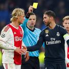 Real Madrid's Sergio Ramos is shown a yellow card by referee Damir Skomina as Ajax's Kasper Dolberg looks on. REUTERS/Wolfgang Rattay