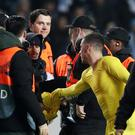 A pitch invader is apprehended by security as Chelsea's Eden Hazard looks on after the match. Action Images via Reuters/Peter Cziborra