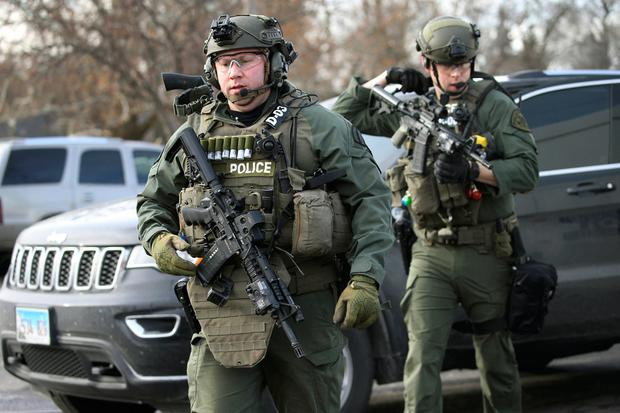 Police officers armed with rifles gather at the scene where an active shooter was reported in Aurora. (Antonio Perez/Chicago Tribune via AP)