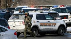 Law enforcement personnel gather near the scene where an active shooter was reported in Aurora, Ill., Friday, Feb. 15, 2019. (Antonio Perez/Chicago Tribune via AP)