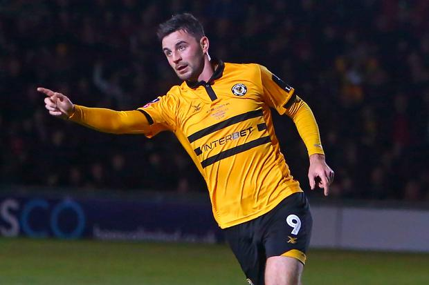 Newport County's Irish striker Padraig Amond celebrates after scoring their goal during the English FA Cup fifth round football match between Newport County and Manchester City at Rodney Parade in Newport, south Wales on February 16, 2019. - Manchester City won the game 4-1. (Photo by GEOFF CADDICK / AFP)