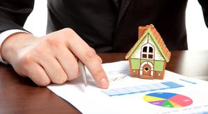 businessman sitting at the table with charts and a house and sign a contract