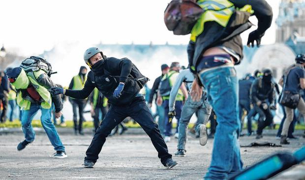 Flashpoint: Protesters wearing yellow vests clash with French riot police in Paris. Photo: Benoit Tessier/Reuters