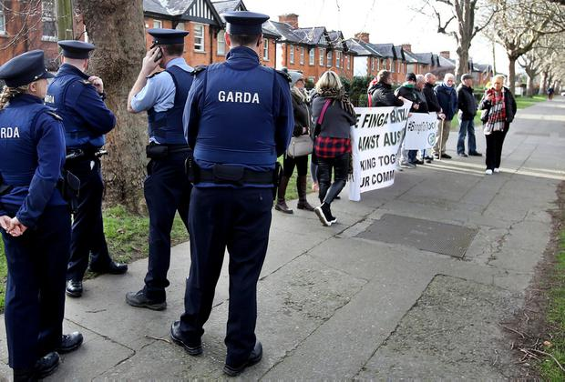 Target: Gardaí and protesters at Richard Bruton's home in north Dublin. Photo: Steve Humphreys