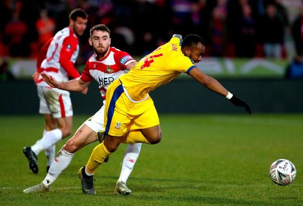 Doncaster Rovers' Ben Whiteman (left) and Crystal Palace's Jordan Ayew (right) battle for the ball. Photo: Richard Sellers/PA Wire