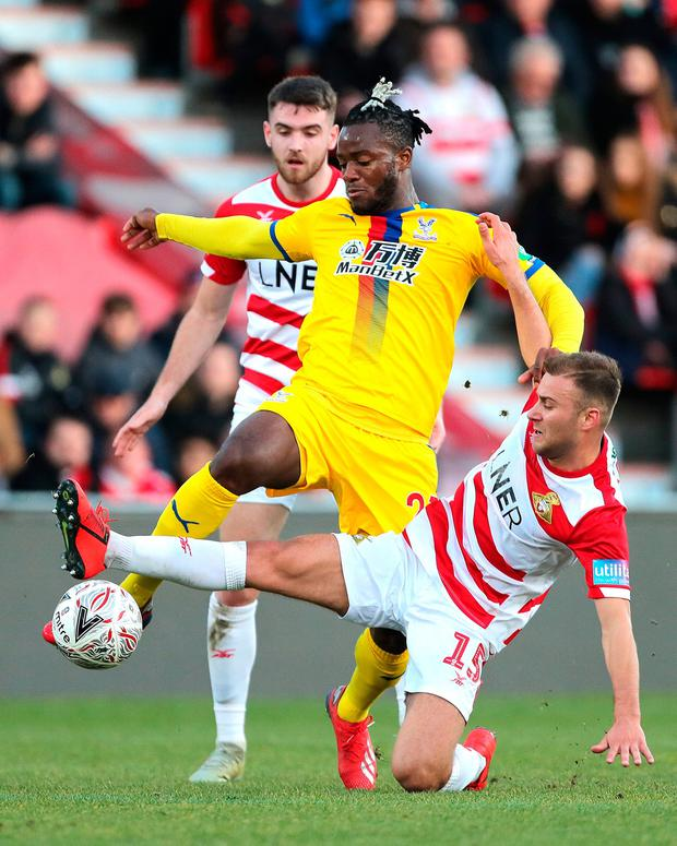 Doncaster Rovers' Herbie Kane slides in on Crystal Palace's Michy Batshuayi (centre). Photo: Richard Sellers/PA Wire