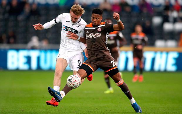 Swansea City's Oliver McBurnie (left) and Brentford's Julian Jeanvier battle for the ball. Photo: Nick Potts/PA Wire