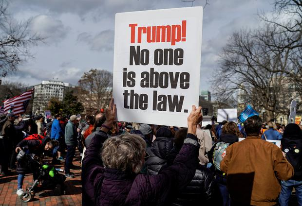 A woman holds a sign during a demonstration against U.S. President Donald Trump on President's Day near the White House in Washington, U.S., February 18, 2019. REUTERS/Joshua Roberts