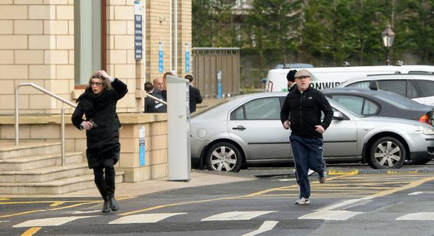 Two men, one disguised as a woman and both carrying handguns, flee the scene of David Byrne's murder. Photo: Sunday World