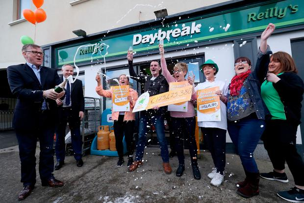 Michale Hayes (left) from the National Lottery sprays champagne as Les Reilly (centre) and the staff of Reilly's Daybreak in Naul, Co Dublin, celebrate selling the EuroMillions ó175 million winning lotto ticket. Photo: Niall Carson/PA Wire