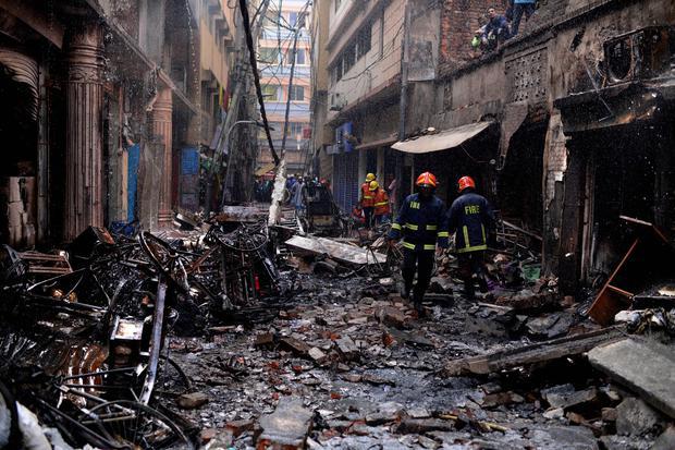 Firefighters gather around buildings that caught fire late Wednesday night in Dhaka, Bangladesh, Thursday, Feb. 21, 2019. A devastating fire raced through at least five buildings in an old part of Bangladesh's capital and killed scores of people. (AP Photo/Mahmud Hossain Opu )