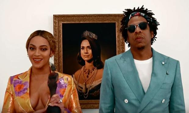 Beyoncé and Jay-Z pose in front of a portrait of Meghan Markle