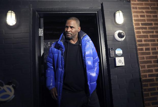 R Kelly emerged from his Chicago studio earlier on Friday night (Abel Uribe/Chicago Tribune via AP)