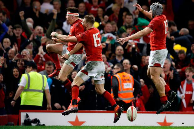 Wales' wing Josh Adams (L) celebrates with Liam Williams (C) and centre Jonathan Davies (R) after scoring the winning try during the Six Nations international rugby union match between Wales and England at the Principality Stadium in Cardiff