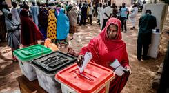 A woman casts her vote at a polling station at the Malkohi refugee camp in Adamawa State in Nigeria. Malkohi is an internal displaced camp for people who fled their homes from areas affected by the conflict with the Islamist terrorist group Boko Haram. Photo: AFP/Getty
