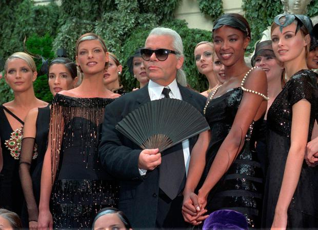 In this Tuesday July 9, 1996 file photo, Karl Lagerfeld is surrounded by Canadian model Linda Evangelista, left, and British model Naomi Campbell, right, and other models after the presentation of his 1996-97 fall-winter haute couture fashion collection for Chanel in Paris