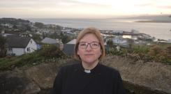 Rev Suzanne Cousins outside St Finian's Church, which overlooks the fishing port of Greencastle in Donegal. Photo: Derry and Raphoe parish