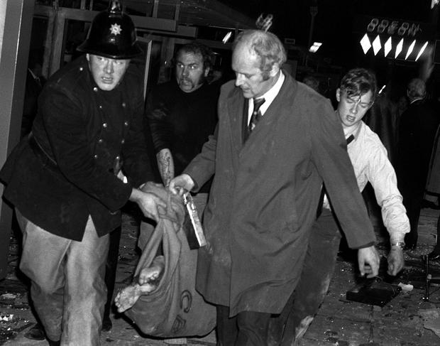 'Terrible events': A fireman and rescue workers carry a barefooted body away from the scene of one of the Birmingham pub bombings in 1974. Picture: PA