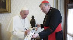 Disgraced: Pope Francis signs a cricket bat with Cardinal George Pell at the Vatican back in 2015. Photo: REUTERS