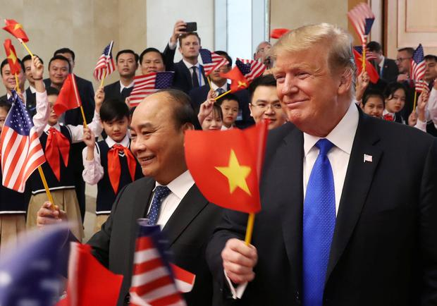 U.S. President Donald Trump and Vietnamese Prime Minister Nguyen Xuan Phuc hold flags as they are greeted by students during their meeting at the Office of Government Hall in Hanoi, Vietnam REUTERS/Leah Millis