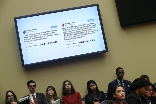 Tweets by U.S. President Donald Trump about Michael Cohen, his former personal attorney, are shown on a television monitor inside the hearing room as Cohen testifies before a House Committee on Oversight and Reform hearing while committee member Rep. Alexandria Ocasio-Cortez (D-NY) looks on in Washington, U.S., February 27, 2019. REUTERS/Jonathan Ernst