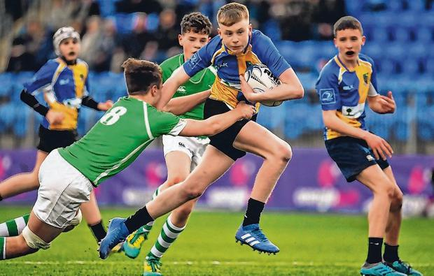 Andrew Osborne of CBS Naas is tackled by Gonzaga's Noah Maguire during the Leinster Schools Junior Cup quarter-final at Energia Park. Photo: Brendan Moran/Sportsfile