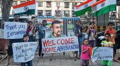 Welcome news: Children hold banners and flags on a street in Mumbai after Pakistan said it would release an Indian air force pilot today. Photo: Francis Mascarenhas/Reuters