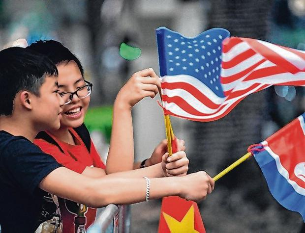Welcome: Children hold US, North Korean and Vietnamese flags near the hotel holding the summit. Photo: Noel Celis/AFP/Getty Images