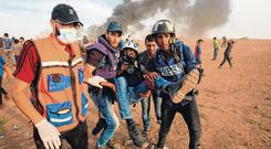Flashback: Journalists carry a wounded colleague during clashes with Israeli forces. Photo: Said Khatib/AFP/Getty