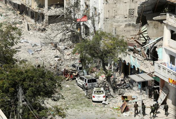 Security personal are seen next to buildings damaged at the scene where a suicide car bomb exploded REUTERS/Feisal Omar