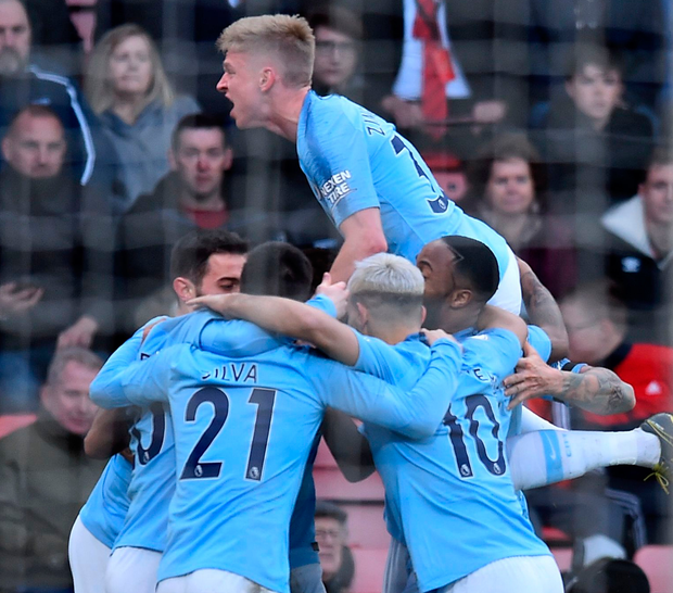 Manchester City midfielder Riyad Mahrez is mobbed by team-mates after scoring the winning goal in the victory over Bournemouth at the Vitality Stadium yesterday. Photo: Getty Images