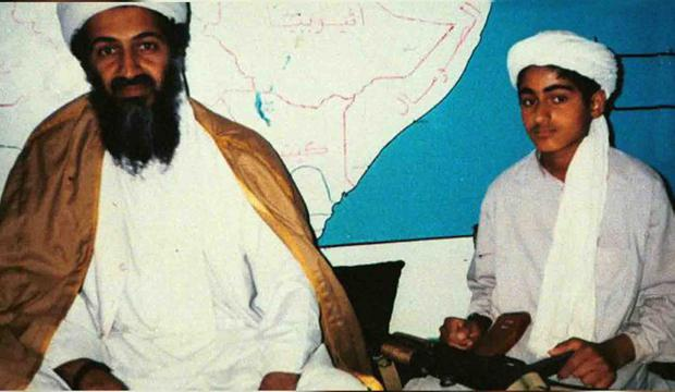 A teenage Hamza bin Laden cradles the AK-47 belonging to his father Osama