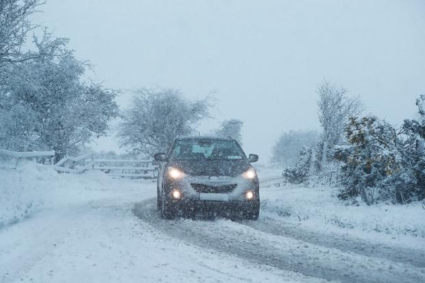 A car is driven through snowfall in the Kilteel area of Dublin Photo credit: Niall Carson/PA Wire