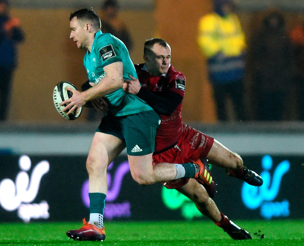 Munster's Rory Scannell is tackled by Ioan Nicholas of Scarlets. Photo: Aled Llywelyn/Sportsfile