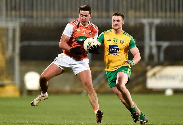 Stefan Campbell of Armagh gets to the ball ahead of Donegal's Leo McLoone. Photo: Oliver McVeigh/Sportsfile