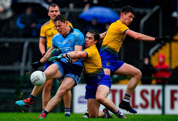 Champions on the charge: Con O'Callaghan scores a point for Dublin despite the efforts of Roscommon's David Murray. Photo: Ramsey Cardy/Sportsfile