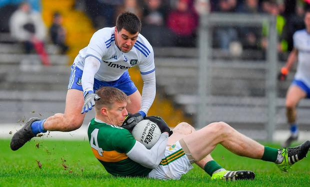 Tommy Walsh holds onto the ball despite the challenge of Monaghan's Drew Wylie. Photo: Brendan Moran/Sportsfile