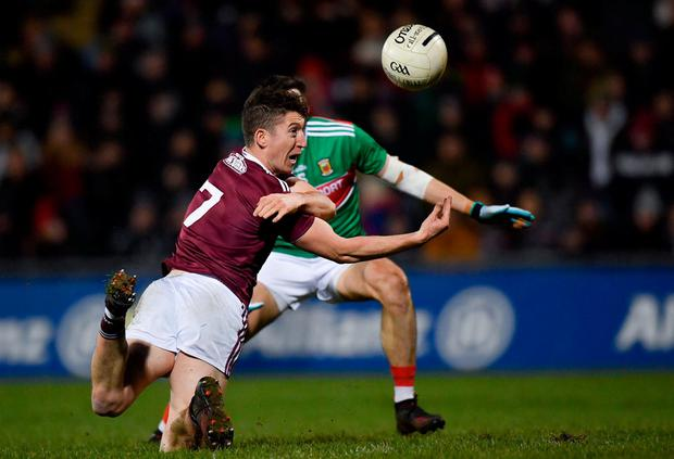 Johnny Heaney of Galway offloads a pass under pressure from Mayo's Jason Doherty. Photo: Piaras Ó Mídheach/Sportsfile