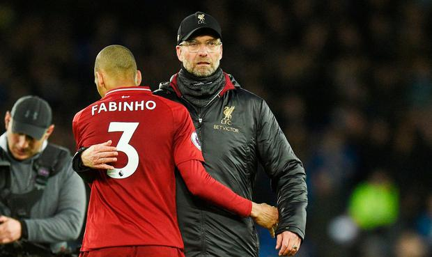 Liverpool's Brazilian midfielder Fabinho (L) is embraced by Jurgen Klopp after drawing the Merseyside detby