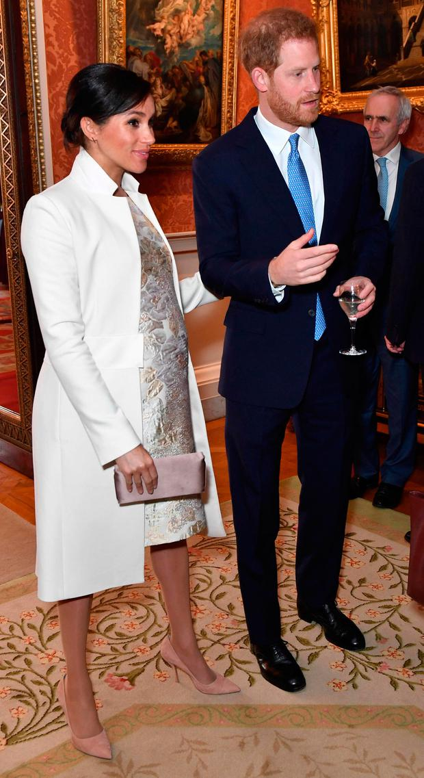 Britain's Prince Harry, Duke of Sussex (R) and Meghan, Duchess of Sussex attend a reception to mark the 50th Anniversary of the investiture of The Prince of Wales at Buckingham Palace in London on March 5, 2019